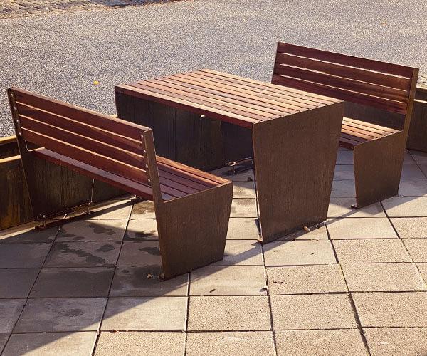 Robust bænk med bord i corten stål med mahogni eller genbrugsplast planker