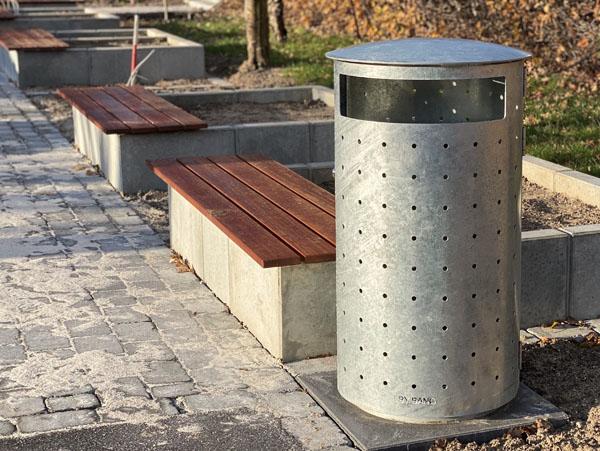 en stor udendørs skraldespand i galvaniseret stål og et originalt design med en betonplanterkasse med et træ sæde