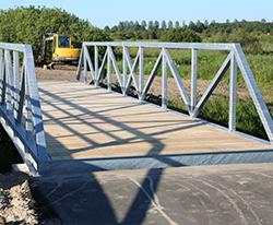 Stibro i Fårup. Cykel og gangbroen er fremstillet i solidt galvaniserset stål med betonanslag i hver ende. Uderumsinventar BY BANG